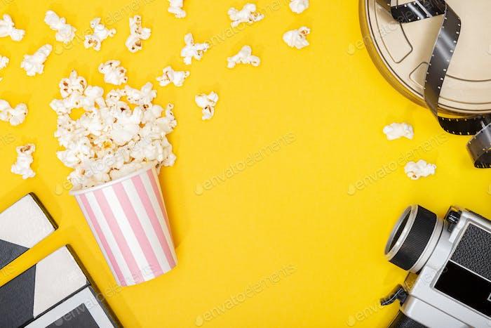 Popcorn Eimer, Filmkamera, Dose und Klapper auf gelbem Hintergrund