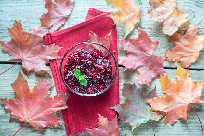 Bowl of cranberry sauce on the wooden board