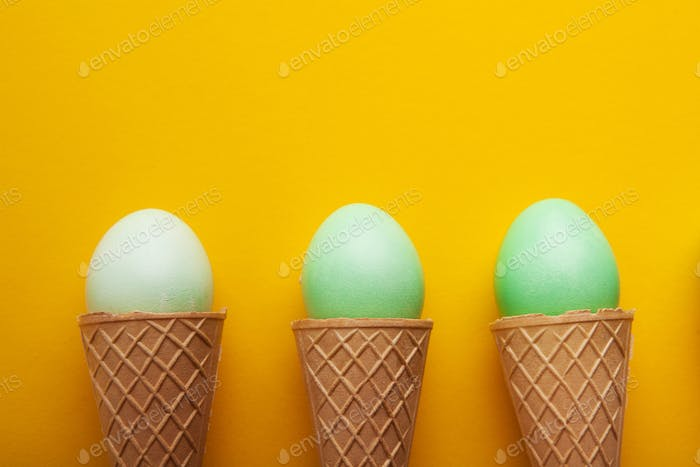 Green easter eggs in waffle cones on yellow background
