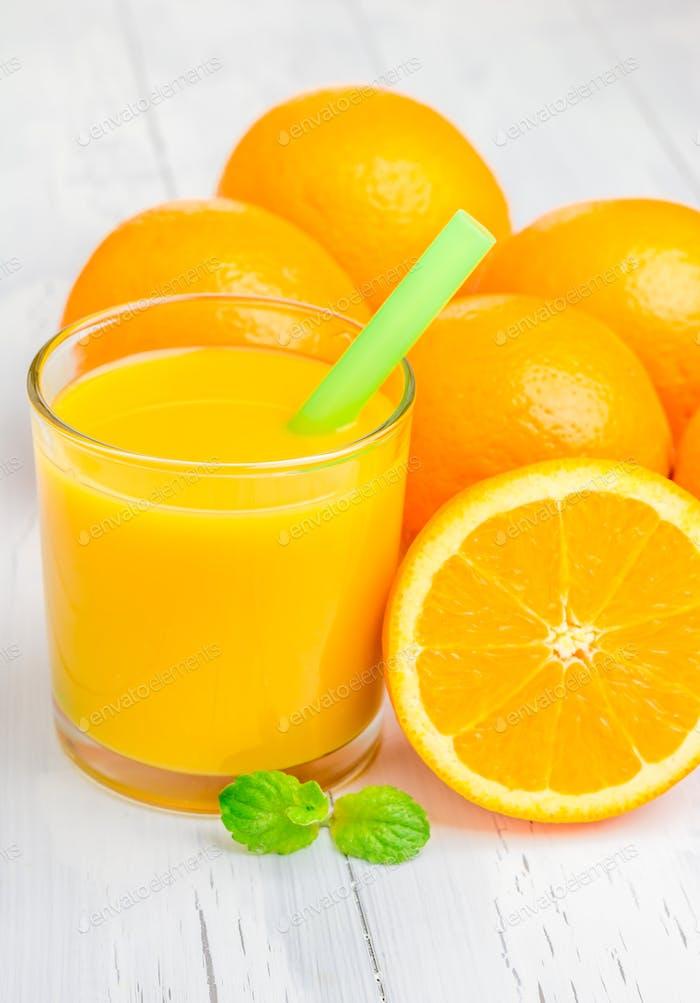Orangensaft und Orangen mit Minze auf weißem Tisch