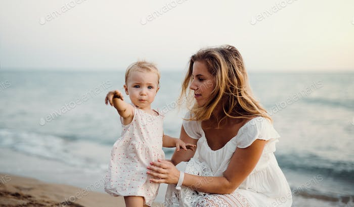Young mother with a toddler girl on beach on summer holiday.