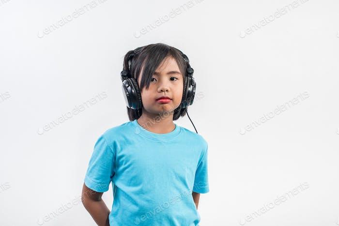 Little girl listening to music on wireless headphones