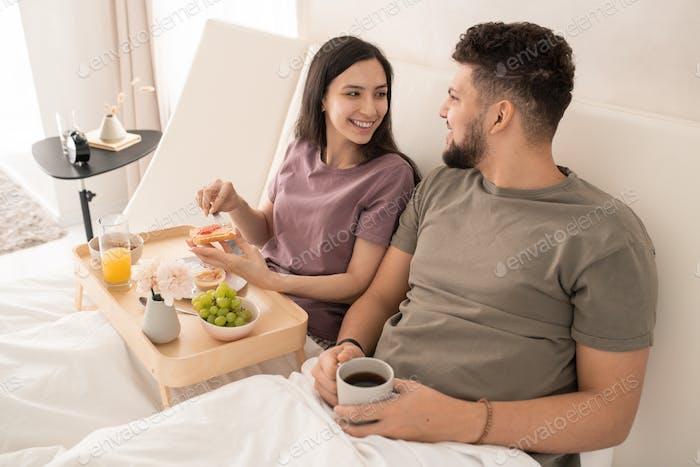Happy female making sandwich for her husband