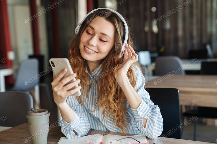 Image of happy young woman using cellphone and wireless headphones
