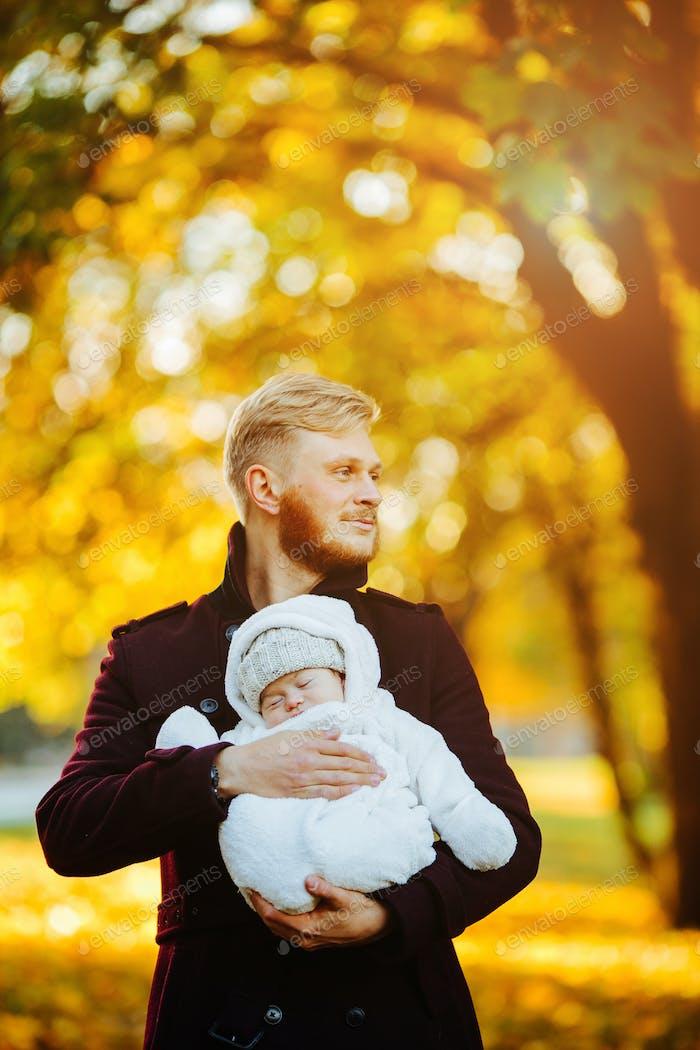 Papa und neugeborener Sohn im Herbst Park