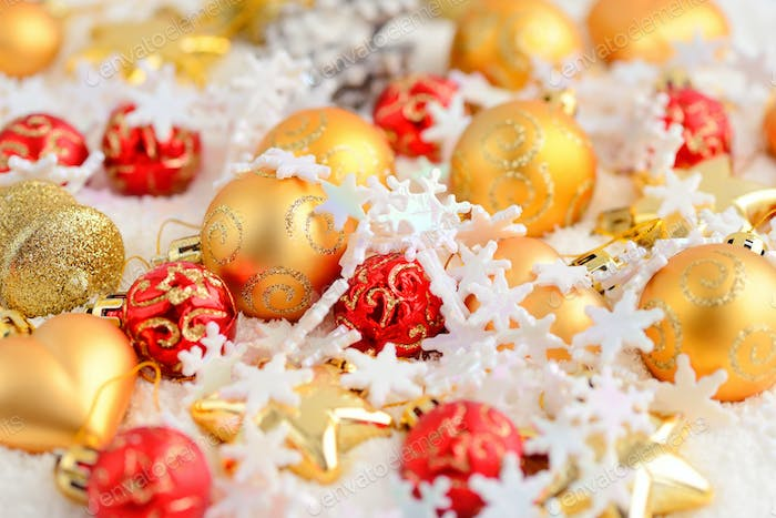 Christmas gold and red ornaments on the snow. Festive Christmas