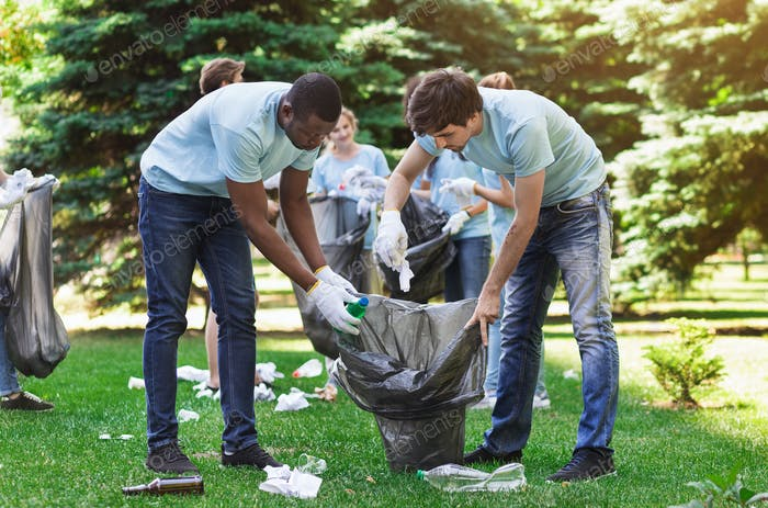 Optimistic volunteers holding garbage bag in park