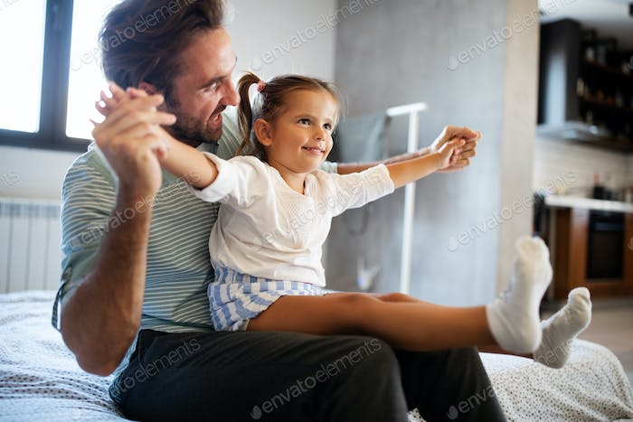Father and his daughter child girl playing together. Happy loving family