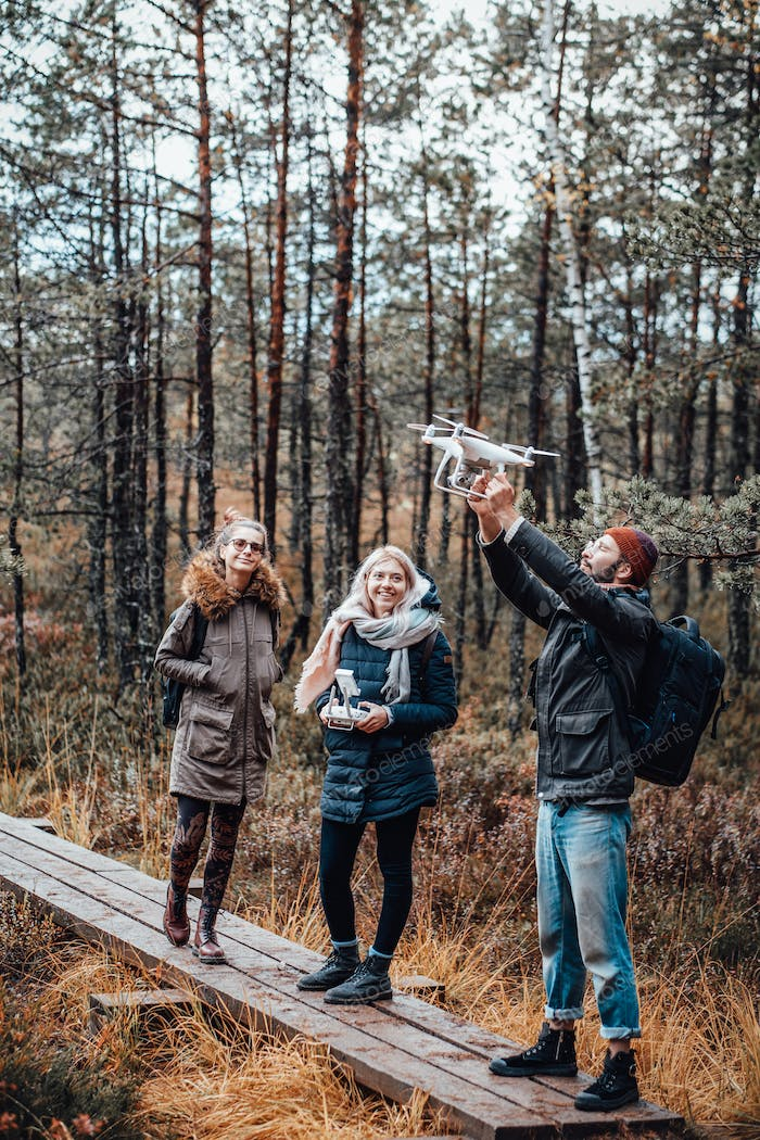 Joyful group of friends with quadcopter in autumn forest