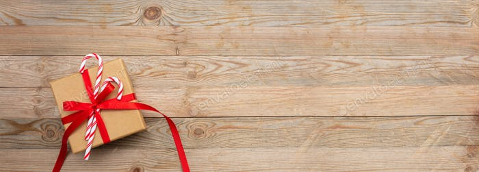A gift box with red ribbon and candy canes on wooden background, banner, copy space, top view