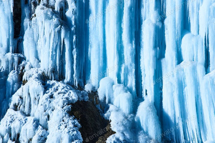 Large icicles hang from river bank cliff.