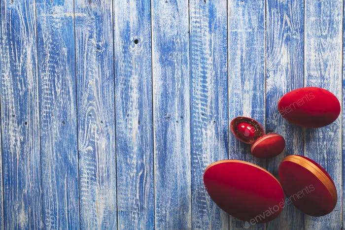 Easter red decorative eggs on a light blue wooden surface