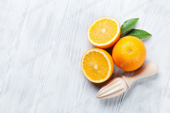 Fresh ripe oranges and juicer