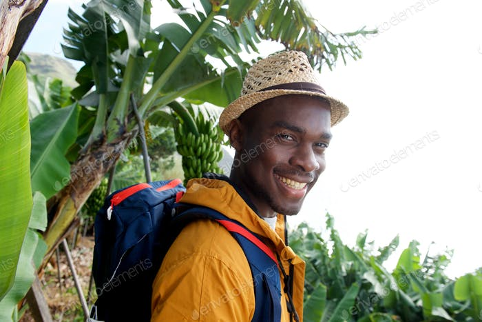 Close up side of happy male traveler with backpack standing in nature