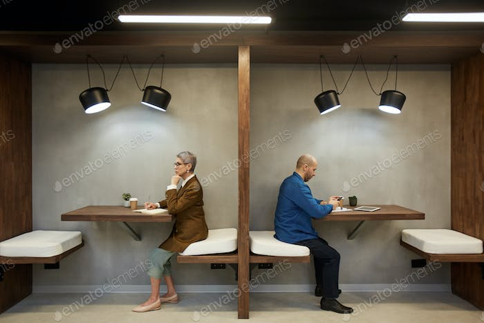 Modern Adult People in Separate Cafe Booths