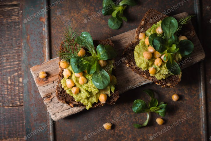Open sandwich with avocado cream and greens  on the metal background top view