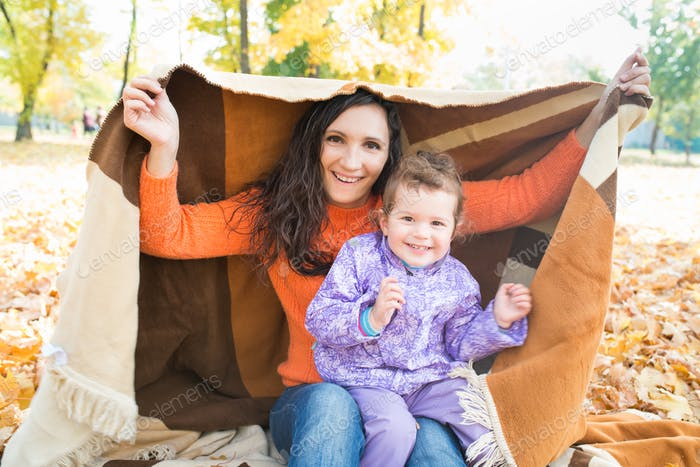 Cute cheerful young mother is covered with plaid