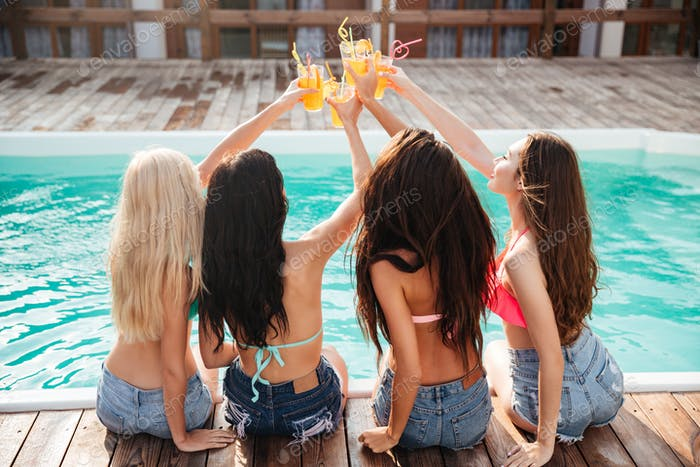 Four girls having fun and drinking cocktails at swimming pool