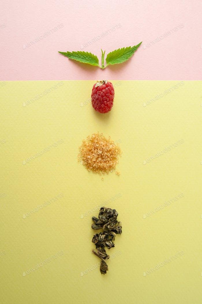 Raspberries, sugar, a mint leaf and a handful of green tea on a