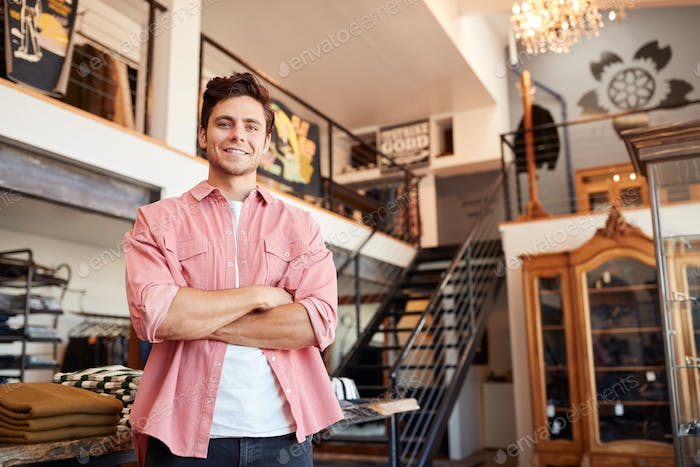 Portrait Of Smiling Male Owner Of Fashion Store Standing In Front Of Clothing Display