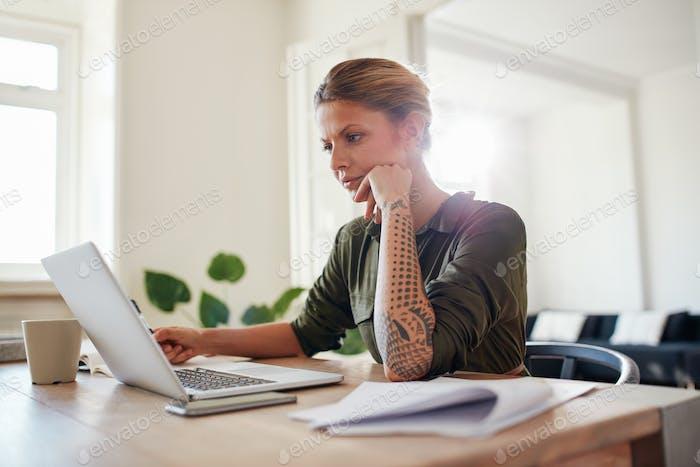 Junge Frau, die Laptop ernsthaft ansieht.