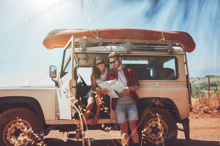 Young couple using map on a roadtrip