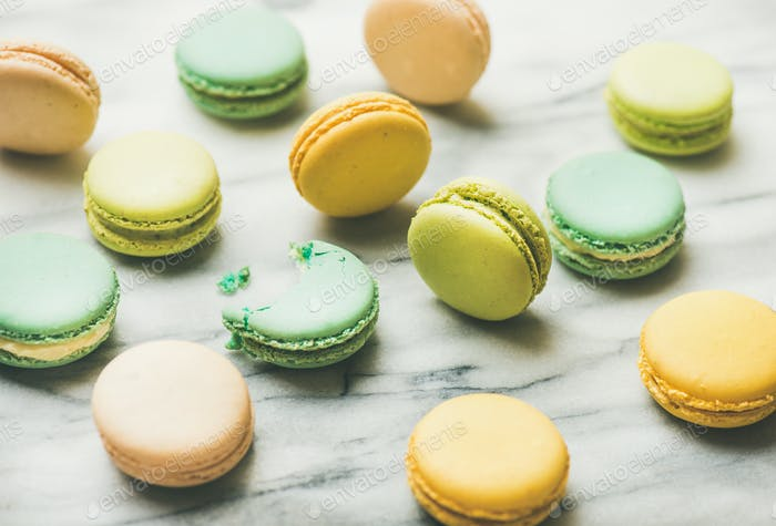 Colorful French macaroons over grey marble background
