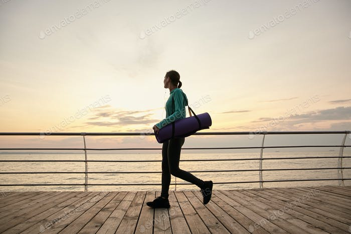 Horizontal photo of walking lady at the seaside in the morning, going to practicing yoga