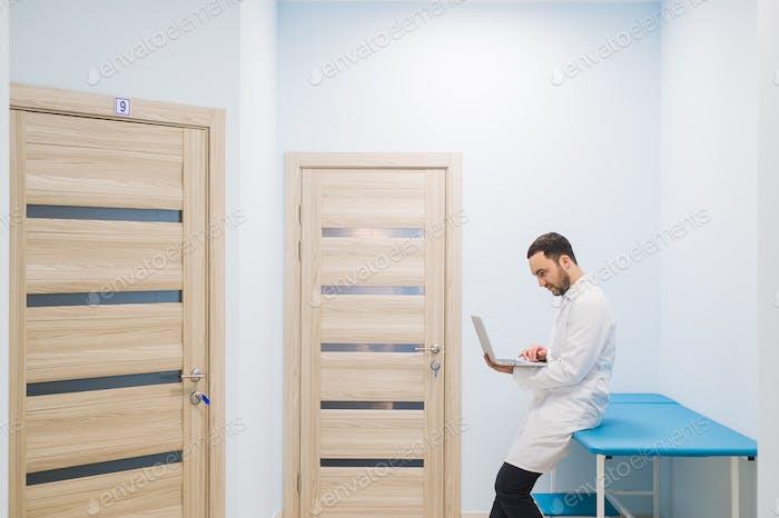 Facharzt im Flur seiner Klinik mit seinem Laptop
