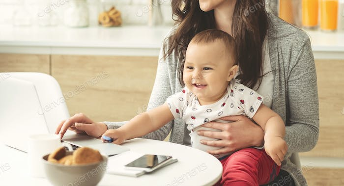 Cute baby boy helping mom to work on laptop at kitchen