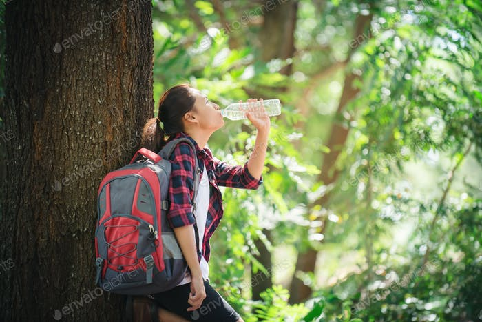 Thirsty woman having a break drinking a bottle of water during hiking in the forest.
