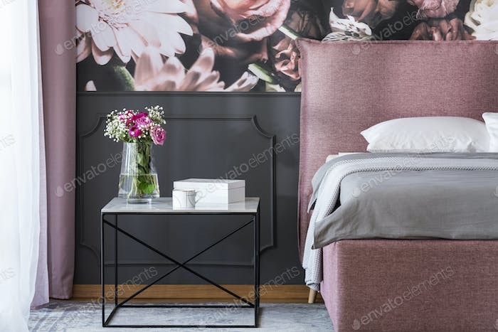 Flowers on black table next to pink and grey bed in bedroom inte