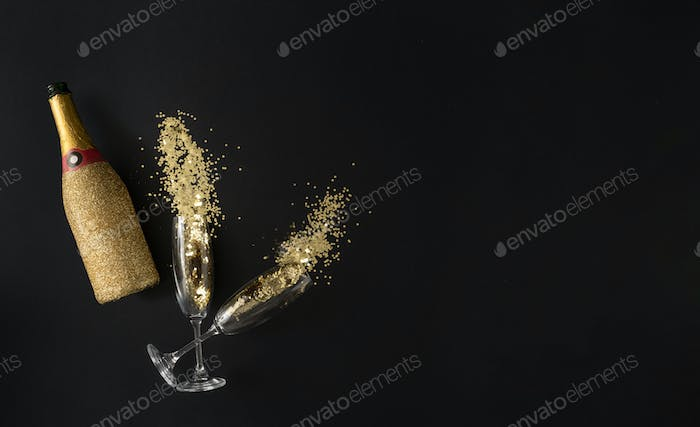 Champagne bottle ald glasses with golden glitter. Celebration party concept. Flat lay