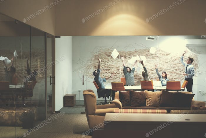 Group of young business people throwing documents