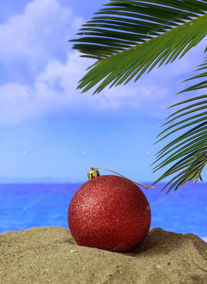 Sommer-Weihnachtsferien Konzept. Weihnachtskugel am Sandstrand mit Palme, blaues Meer
