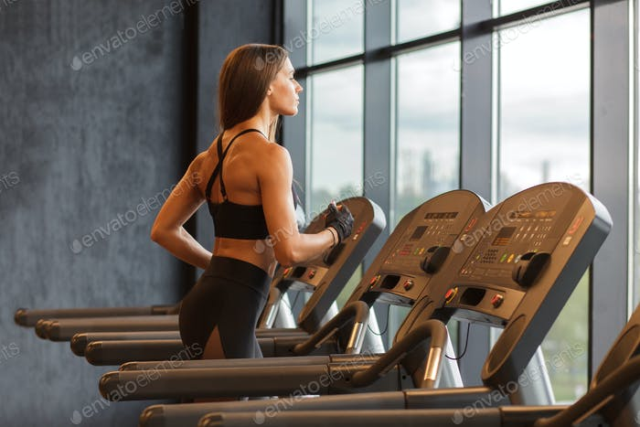 young hispanic athletic sportswoman on treadmill