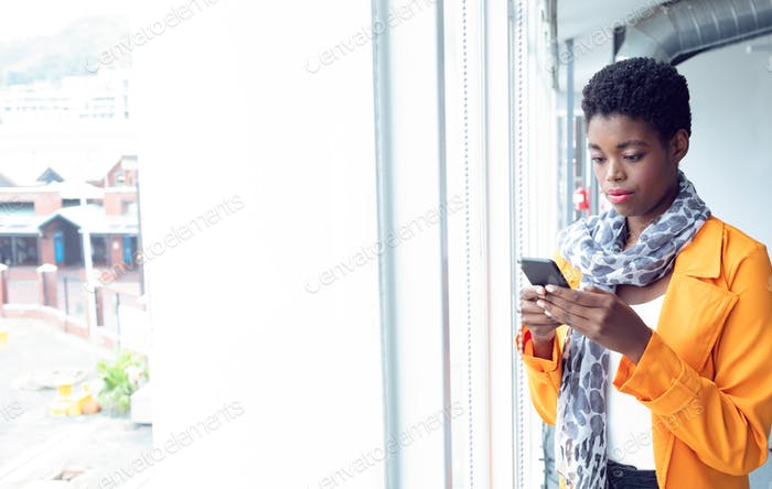 Portrait of young African-american Businesswoman using mobile phone near window in office