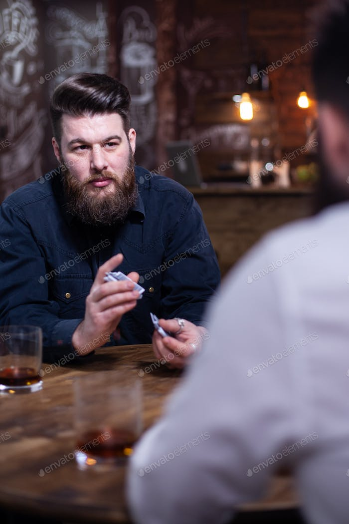 Handsome bearded man looking at his friend and shuffle cards