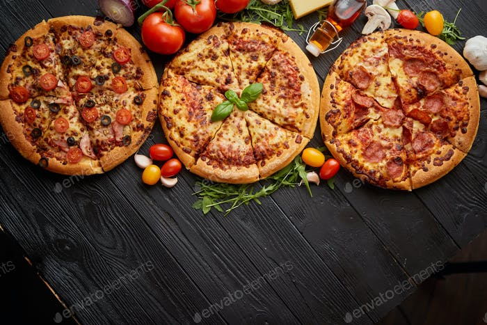 Frisch serviert, drei verschiedene Pizzen unter leckeren Zutaten platziert. Ansicht von oben
