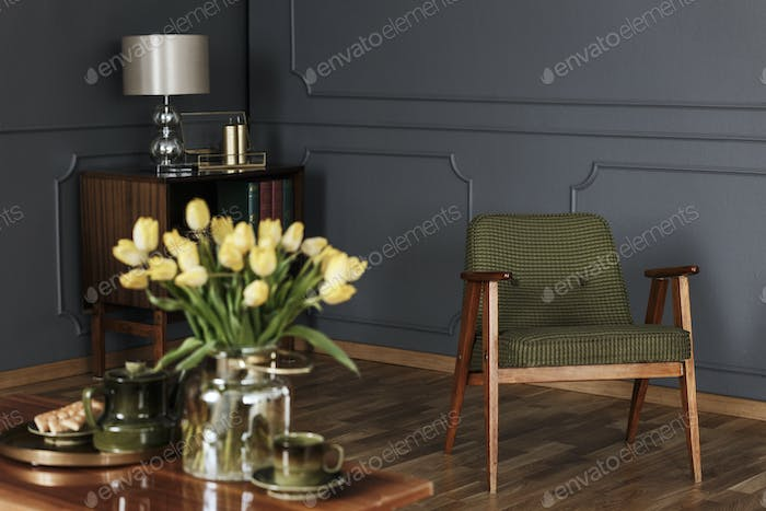 Real photo of a green, old-fashioned armchair in living room int