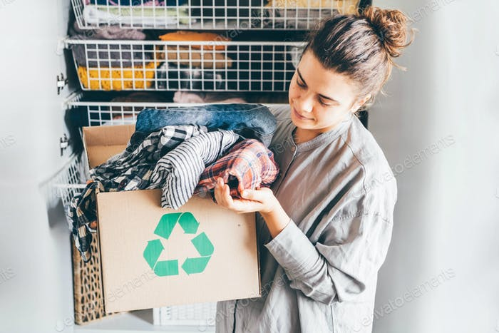 Recycle clothes concept. Young woman with recycling box full clothes.