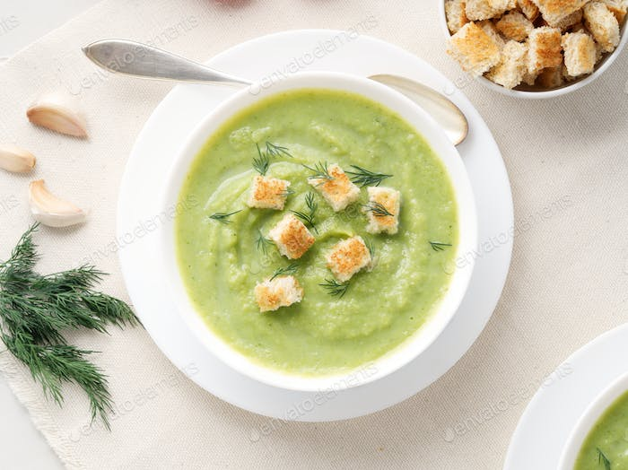 large white bowl with vegetable green cream soup of broccoli, zucchini, green peas on white