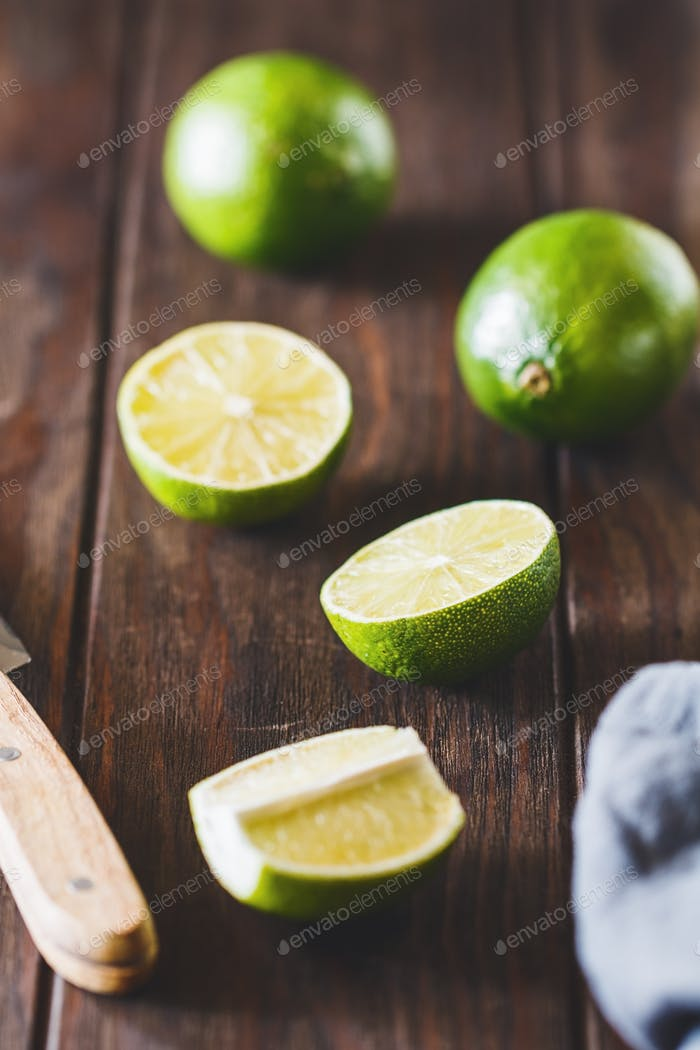 Cutting lime wedge on a wooden kitchen table. Rustic style food photography.