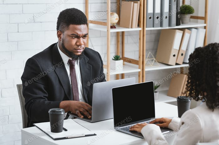 Workplace conflict. Displeased African American guy having disagreement with his female colleague at