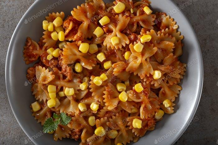Italian pasta farfalle with tuna, corn and tomato sauce