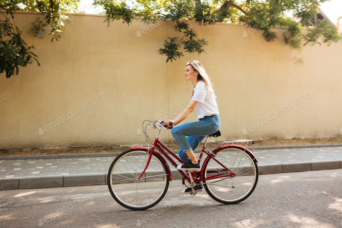 Beautiful girl with blond hair happily riding bicycle