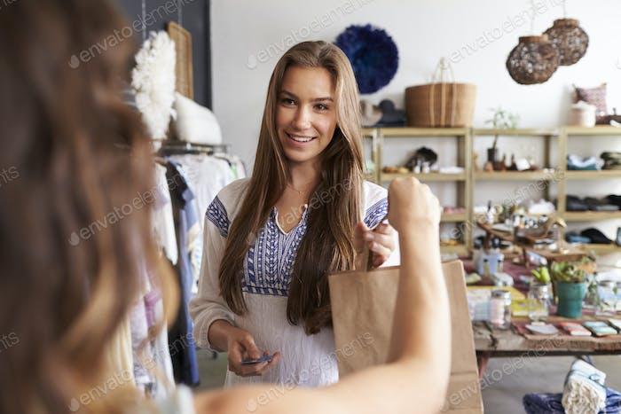 Junge weibliche Kundin nimmt Tasche von Assistentin in einer Boutique
