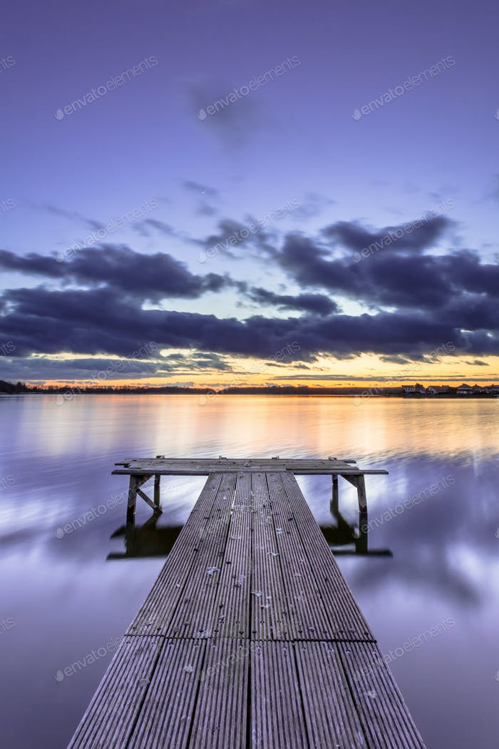 Purple Colored Sunset over Tranquil Lake with Wooden Jetty