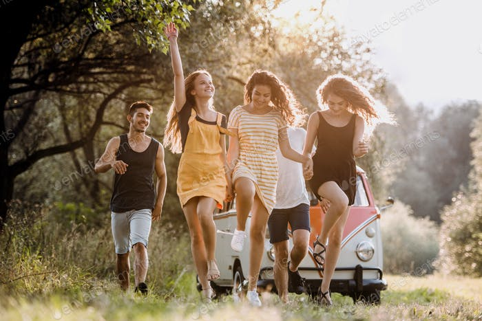 A group of young friends on a roadtrip through countryside, jumping.