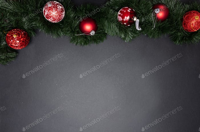 Xmas bauble shiny red color against grey black background, high angle